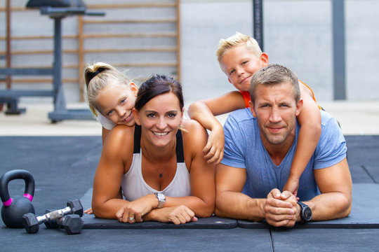 Happy family exercising in gym