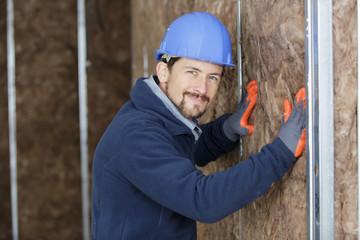 Fototapeta builder in protective helmet and gloves doing insulation works obraz