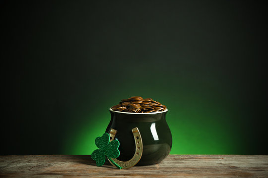 Pot with gold coins, horseshoe and clover on wooden table against dark background. St. Patrick's Day celebration