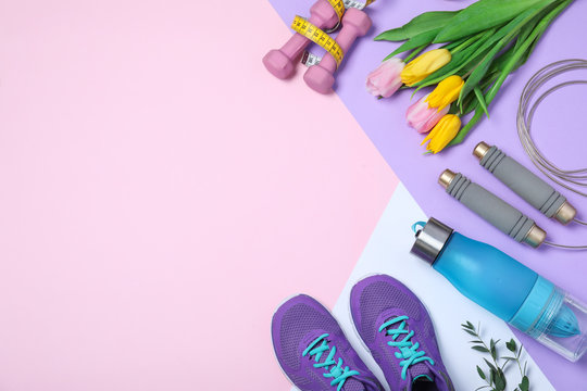 Flat lay composition with spring flowers and sports items on color background. Space for text