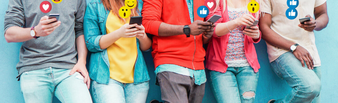 Group of millennial friends using mobile phones - Young people addiction to technology trends following and chatting with emoji on smartphones - Tech and millennial concept - Focus on center hands