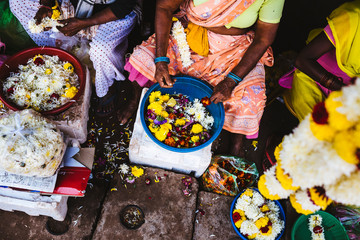 High angle close up of women lacing flowers on strings at a market.,Goa