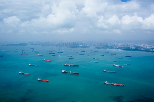 High angle view of barges and cargo ships in a bay, cityscape in the distance.