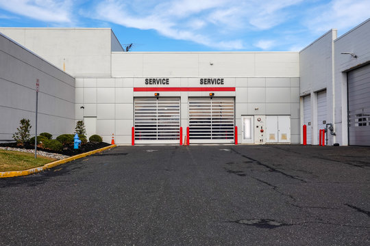 Two overhead garage doors with the word service over each on the side of a white building