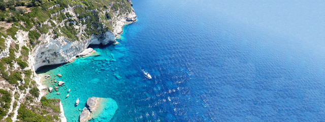 Aerial drone ultra wide photo of breathtaking turquoise exotic bay of blue lagoon in island of Paxos visited by sail boats, Ionian, Greece