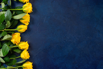 Top view of beautiful yellow roses on dark blue background Fotobehang