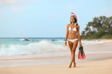 Beach vacation sports fit bikini woman Asian beauty model relaxing walking with snorkel mask and swim fins scuba equipment rental for water sport leisure activity. Active life.
