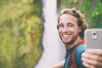 Selfie travel tourist man taking photo with phone on adventure hike vlogging for online social media influencer. Hawaii waterfall sightseeing. Smiling backpacker guy using mobile on summer vacation.