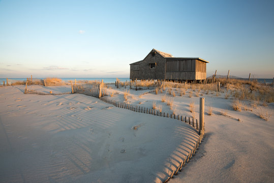 Serene, sunset beach scene of a structure from 1911 still standing on sand dunes with beautiful sea grass, on the shoreline of the Atlantic Ocean, New Jersey