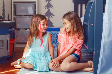 Two cute little Caucasian girls siblings sitting on floor at home room. Happy smiling friends relationship concept. Adorable children playing together. Authentic candid lifestyle domestic life moment.