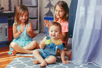 Caucasian girls siblings sitting on floor at home and playing with a sister toddler. Happy friends relationship concept. Adorable children playing together. Authentic candid lifestyle moment.