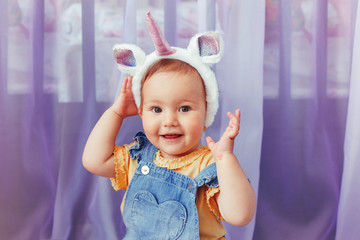 Cute adorable Caucasian baby girl wearing unicorn headband with horn and ears. Pretty funny child kid with head hair fairy tale animal accessory toy. Smiling toddler playing at home looking at camera