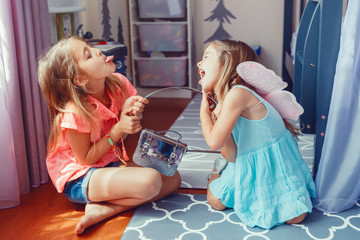 Two little mad angry girls sisters having fight at home. Friends girls can not share toy. Lifestyle authentic funny family moment of siblings quarrel life. Kids bad behaviour.