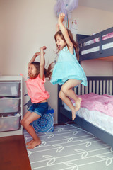 Two cute Caucasian girls siblings jumping from bed in room. Happy excited friends having fun at home. Adorable children playing together. Authentic action candid lifestyle domestic life moment.