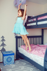 Cute Caucasian girl jumping from bed. Happy excited kid having fun at home. Adorable child playing game flying like an elf or fairy. Authentic action candid lifestyle domestic life moment.