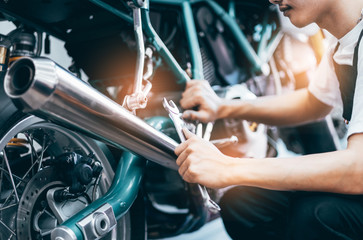 Bike repair. Young man repairing  motobike in garage.mechanic fixing motocycle engine.Serious young man repairing his motorcycle in bike repair shop. Papier Peint