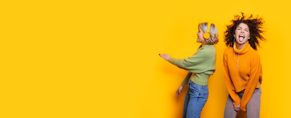 Two cheerful caucasian women with curly hair dancing and listening to music with headphones posing on yellow copy space