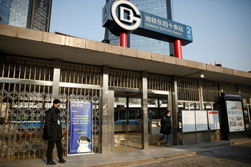 A staff member wearing a face mask stands next to a banner advising subway passengers to cooperate with body temperature measurements and wear masks, as the country is hit by an outbreak of the new coronavirus, outside a subway station in Beijing