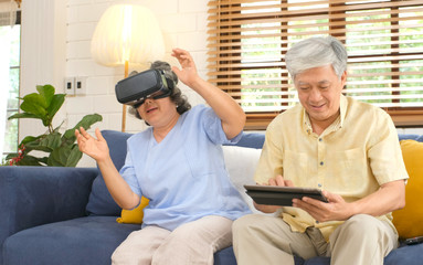 Senior asian couple playing virtual reality headset and using digital tablet in home living room with happiness, Asia elderly retirement old people lifestyle and technology