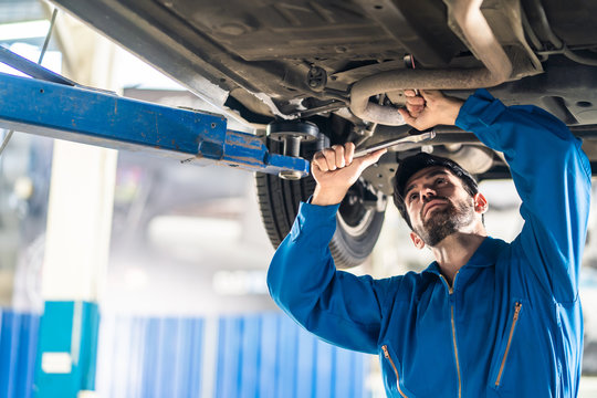 Vehicle service maintenance handsome mens checking under car condition on lifter hoist in garage. Automotive mechanic man use tool to tighten and replace damaged or broken part. Repair service concept