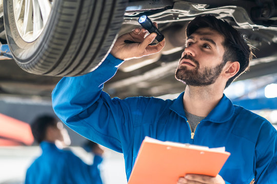Vehicle service maintenance handsome man checking under car condition in garage. Automotive mechanic pointing flash light on wheel following maintenance checklist document. Car repair service concept