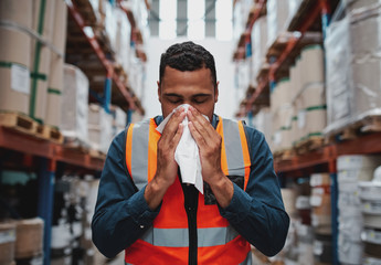 Young sick african warehouse worker blowing nose while working wearing safety vest Wall mural