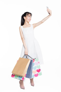 happy young woman with shooping bags taking a selfie.