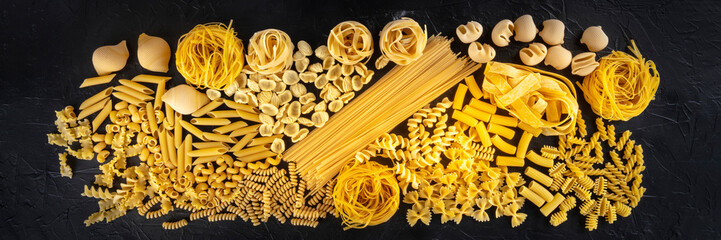 Italian pasta panorama, a flat lay texture of many different pasta kinds, shot from the top on a black background Fotomurales