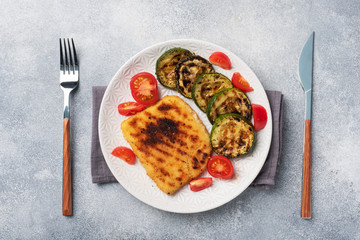 Schnitzel of chicken and zucchini cooked on the grill. Fresh tomatoes on a plate. Ready delicious dinner lunch.