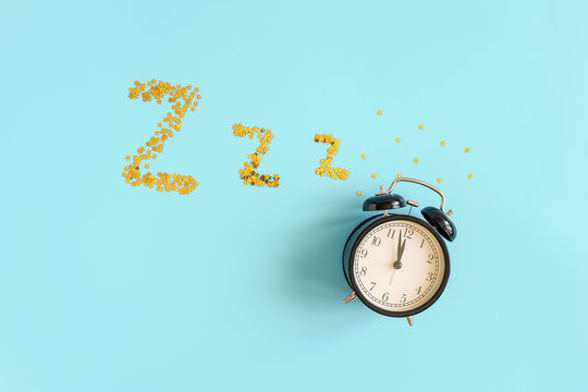 Black alarm clock and gold stars confetti in form of dream symbols Z Z Z on blue background. Top view Copy space. Concept Insomnia, sleep problems or sweet dreams and good night.
