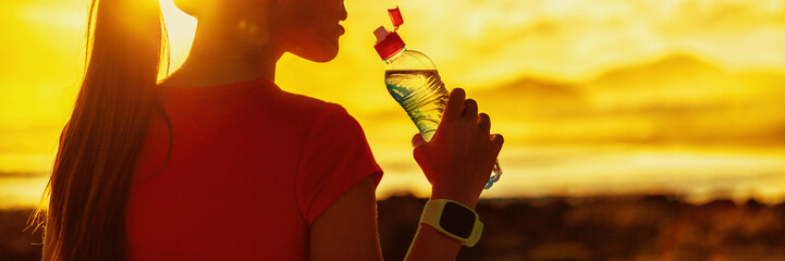 Dehydrated runner fitness woman drinking water bottle sports drink on summer heat workout after run training jogging outdoors at sunset panoramic banner. Girl running silhouette against sun flare.