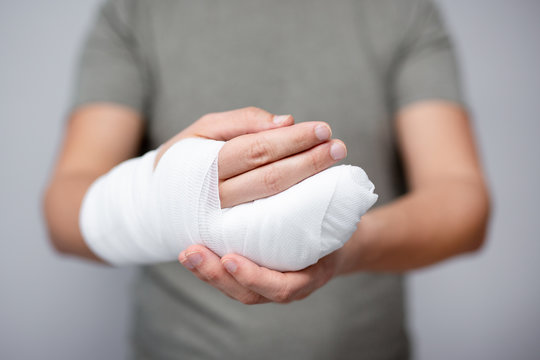 first aid concept - close up of male hand with bandage and gypsum