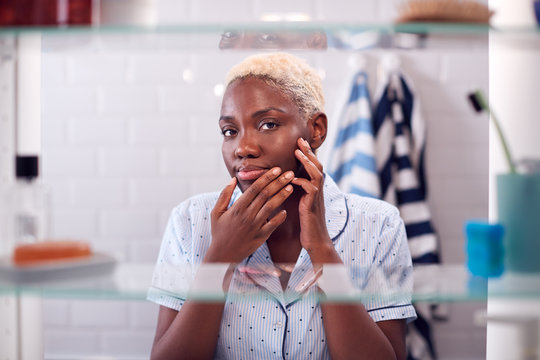 View Through Bathroom Cabinet Of Young Woman Squeezing Spot Before Going To Work