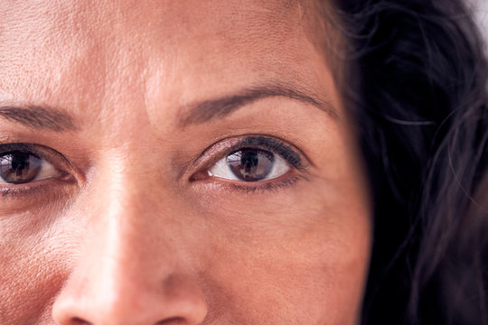 Close Up On Eyes Of Smiling Mature Woman In Studio