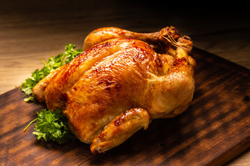 Roasted whole chicken on wooden cutting board