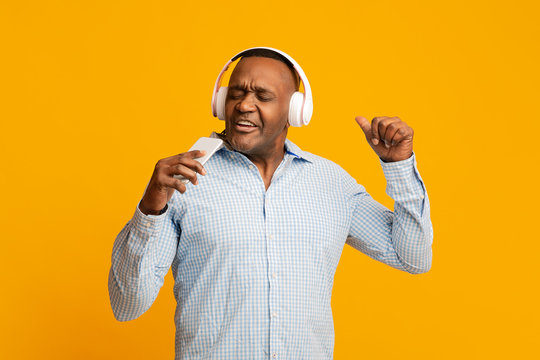 Emotional african mature man in headphones singing at phone