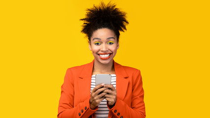 Wall Mural - Afro girl holding cell phone in yellow studio