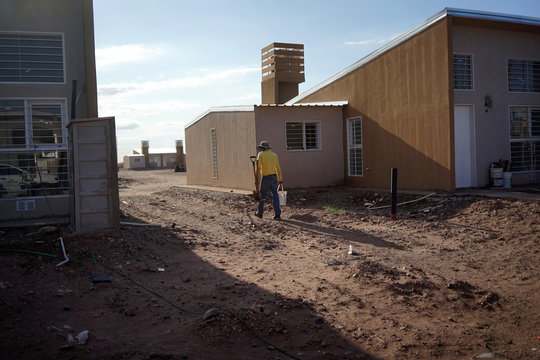 A worker carries tools at the construction site of a housing complex, in Anelo