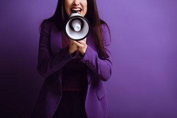 cropped view of excited woman screaming in megaphone on purple background