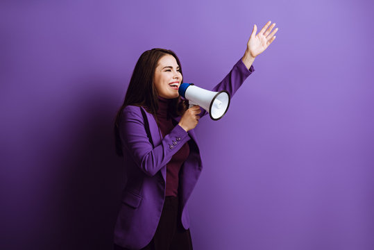 excited young woman talking in megaphone while standing with raised hand on purple background