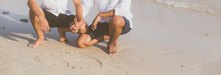 Young asian couple gay romantic drawing heart shape together on sand in vacation, homosexual happy and fun with love sitting on sand at the beach in travel summer, LGBT legal concept, banner website.