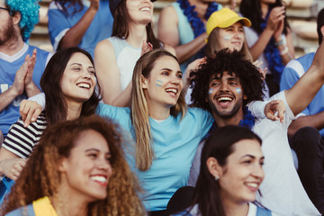Happy Argentinian soccer fans watching a match in stadium Fotobehang