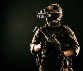 Army elite soldier with hidden behind mask and glasses face, in full tactical ammunition, looking aside, equipped night vision device, radio headset, armed short barrel rifle studio contour shot