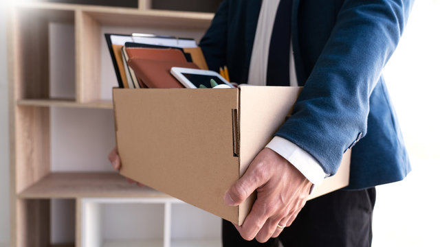Businessmen are holding resignation document and packing personal company on brown cardboard box changing work, resign concept