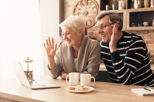 Happy senior couple looking at laptop screen in kitchen and waving