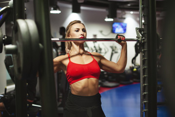 Poster Fitness Beautiful young athletic woman is training in the gym. A girl in sportswear performs exercises with a barbell. Workout, sport, fitness, style, lifestyle