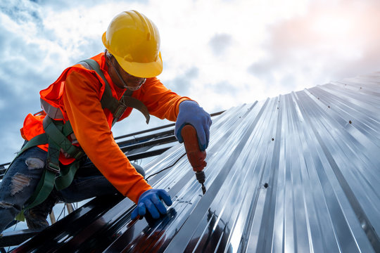 Close up photo of Professional and qualified roofer in protective uniform wear use electric drill to install the metal sheet on the new roof of new modern building construction.