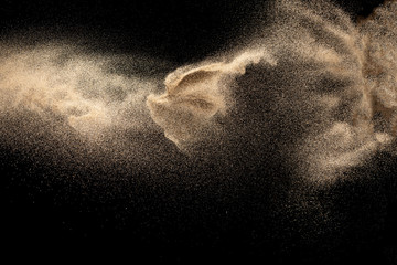 Brown colored sand splash.Dry river sand explosion isolated on black background. Abstract sand cloud. Fototapete