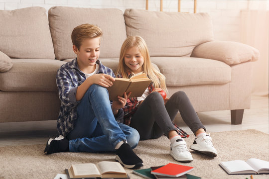 Siblings Reading Book Learning Together Sitting On Floor Indoor
