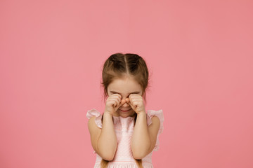 upset little child girl is crying on pink background. girl wiping tears